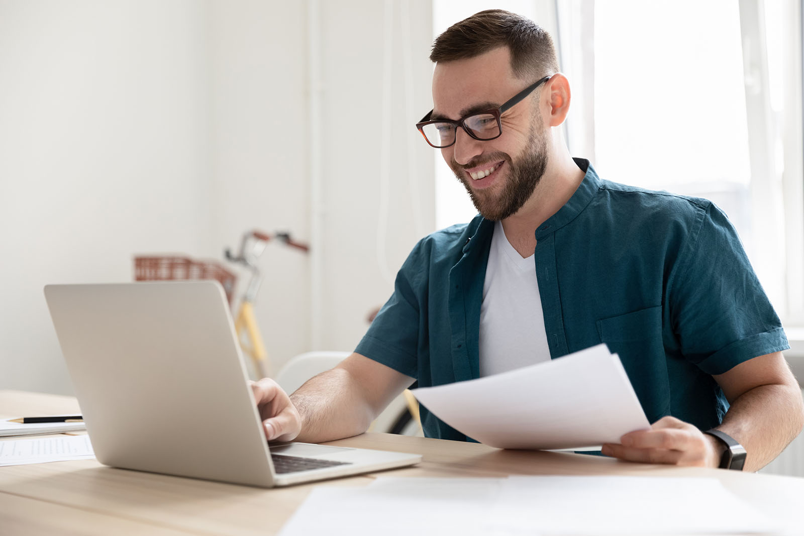 Happy young businessman in eyeglasses working on computer.