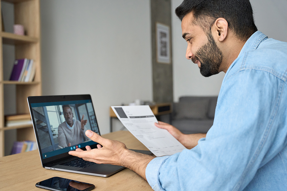 Young indian businessman having video call talking to potential employee.